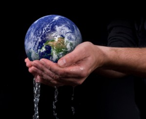 Hands holding the earth while water spills from the hands
